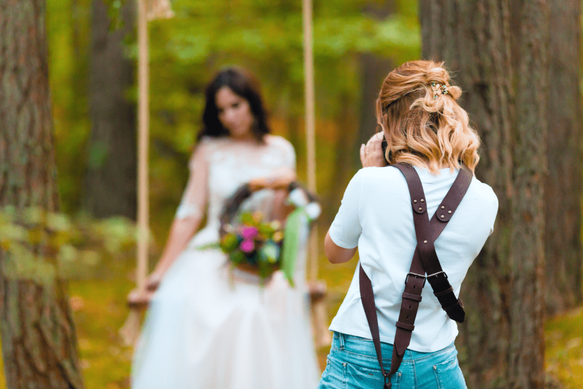 Wedding photographer photographing bride on swing